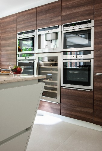 Dark wooden cupboards with integrated appliances in modern kitchen