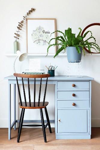 Typewriter on retro desk and fern on white wire stand