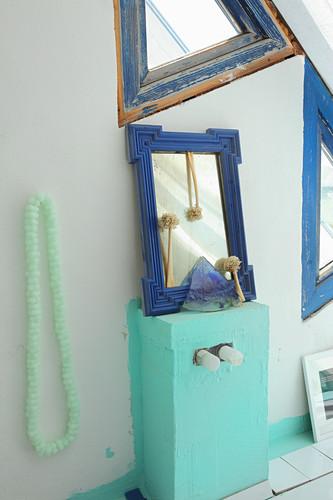 Blue-framed mirror on mint-green cabinet