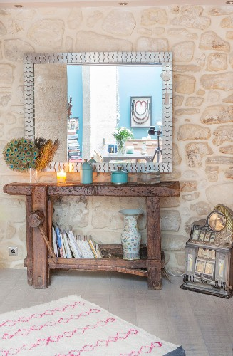 Large mirror above old workbench against stone wall