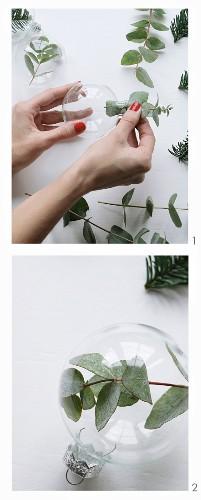 Blätter- und Tannenzweige in Glaskugeln stecken