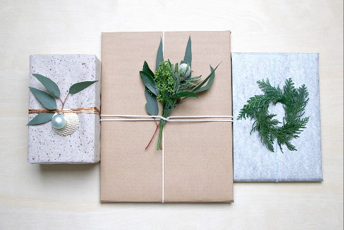 Wrapped gifts decorated with twigs, leaves and Christmas baubles