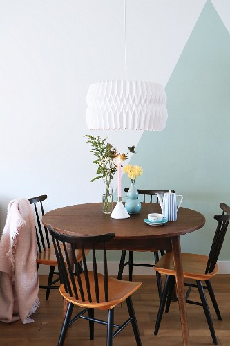 Round table and old chairs in front of two-tone wall