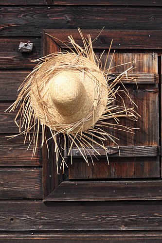 Hand-made straw hat hung on wooden wall