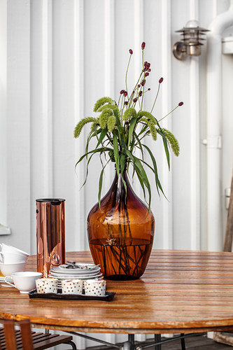 Brown glass vase and coffee set on wooden table outside house