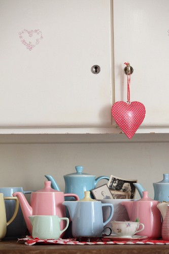 Collection of retro pastel jugs on kitchen dresser with heart-shaped pendant on cupboard door
