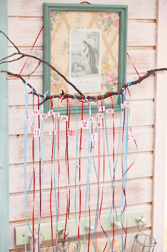 Hand-made Advent calender with numbered ribbons hung from branch below religious icon