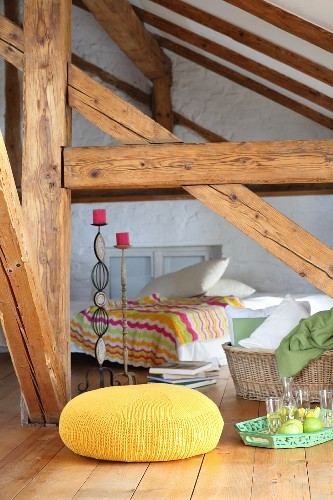 Yellow knitted pouffe in attic room of half-timbered house