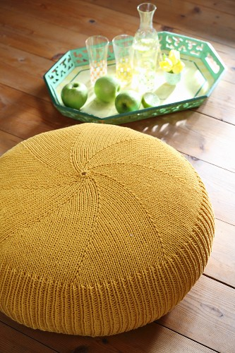 Yellow knitted pouffe next to apples and glasses on green tray
