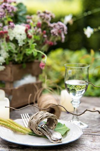 Cutlery in wicker napkin ring on rustic garden table