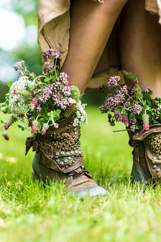 Girl with bunches of wildflowers stuffed in studded leather boots