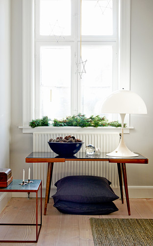Designer lamp on retro table in front of window with conifer branches on sill