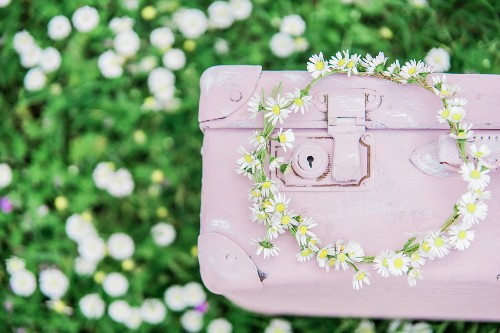 Wreath of daisies on pink suitcase on lawn