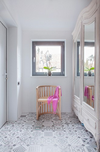 Semicircular chair next to classic wardrobe on patterned floor