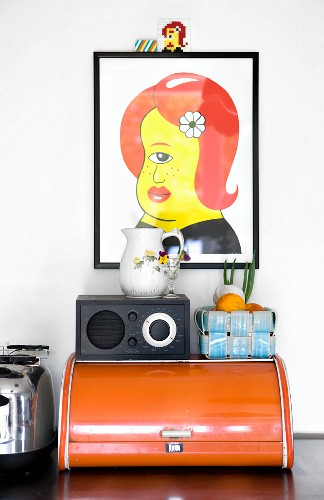 Colourful artwork above radio and fruit basket on top of old bread bin