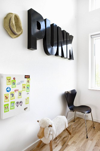 Decorative letters on wall above rocking sheep and chair