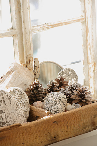 Pebbles covered with lace and pine cones in old wooden crate