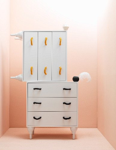 White chests of drawers against pink wall