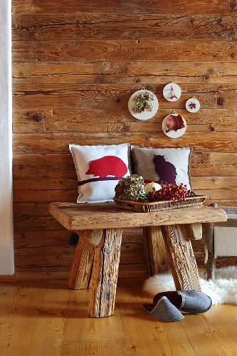 Small artworks made from felt remnants on wooden wall and cushion covers with felt motifs in cabin-style interior