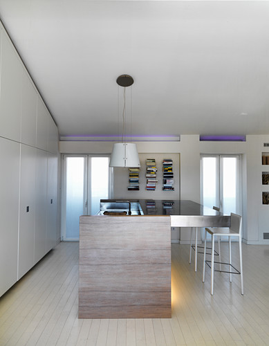 Open-plan kitchen with fitted cupboards below sloping ceiling