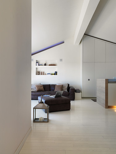 Open-plan interior with fitted cupboards below sloping ceiling