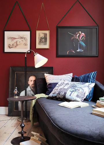 Eklektische Leseecke mit Stehleuchte vor gerahmten Bildern an roter Wand
