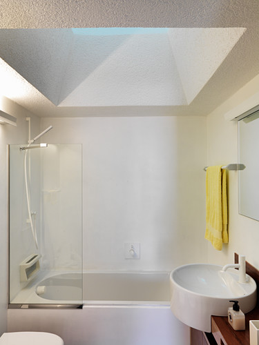 Shower tub below skylight in small bathroom