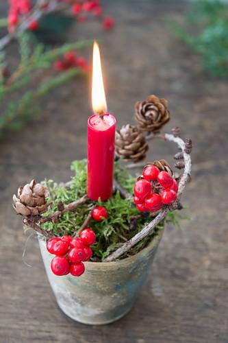 Tontopf mit Moos, Kerze, Ilex und Lärchenzapfenzweig als Weihnachtsdeko