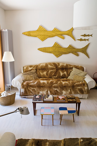 Blanket on sofa below sculptures of fish on wall, coffee table and side tables in living room