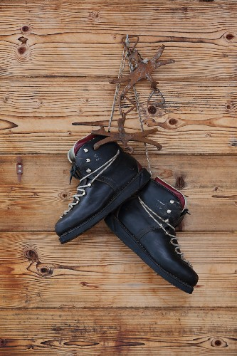 Walking boots hung on wooden façade