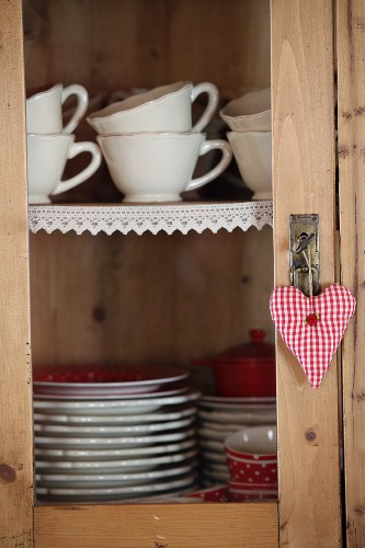 Cups and plates in cupboard with lace trim on shelves