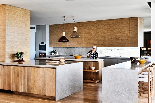 Kitchen units with wooden fronts and limestone worktop in open kitchen, woman in background