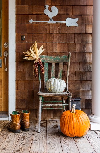 Pumpkins, dried maize cobs and boots on porch in autumn