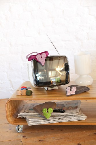 Mouse-shaped dusters hand-sewn from fleece and cotton fabrics on TV cabinet