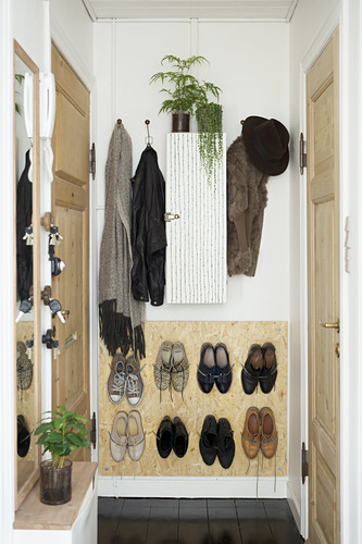 Wall-mounted shoe rack on board in narrow hallway
