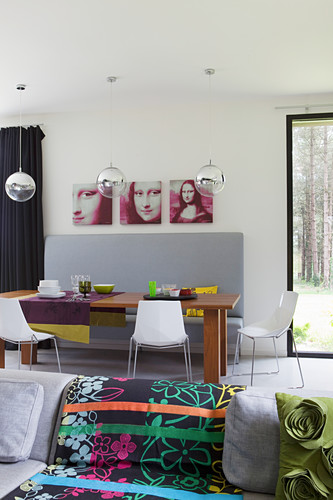 View across sofa with colourful blanket to dining area with grey bench and Mona-Lisa triptych