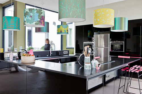 Black modern kitchen area in centre of room below colourful lampshades