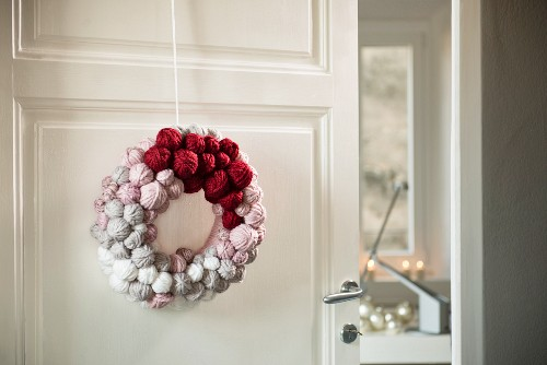 Hand-made door wreath decorated with small balls of wool