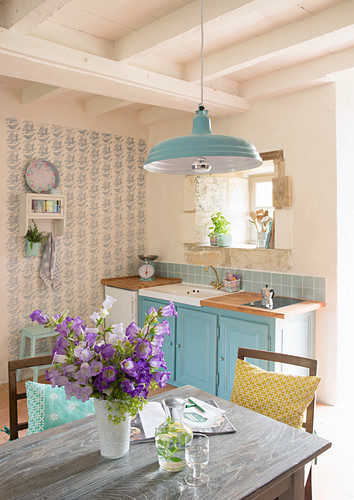 Vase of flowers on table in country-house kitchen