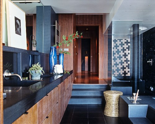 Washstand with charcoal-grey counter and wooden front in elegant bathroom