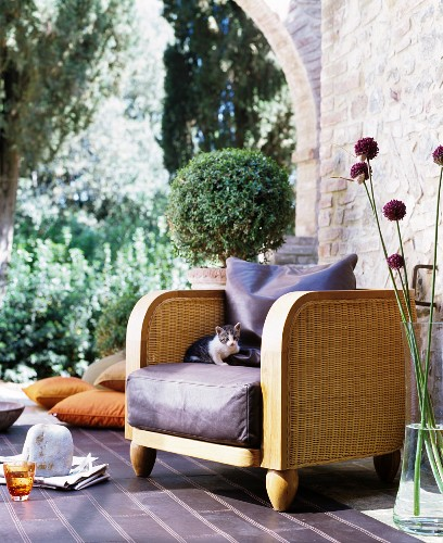 Elegant wicker armchair with leather seat cushion next to glass vase and brick wall