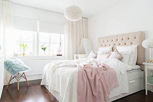 Double bed with button-tufted headboard in bedroom in white and pastel shades
