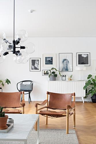 Scandinavian chairs with leather seats and backs in front of gallery of pictures