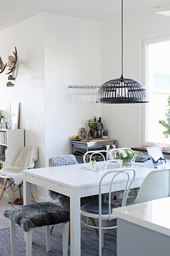 White table and various chairs in open-plan interior