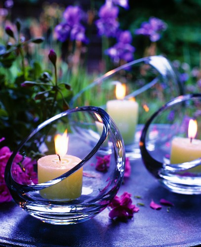 Atmospheric table decorations: Lit candles in glass bowls with angled openings at twilight