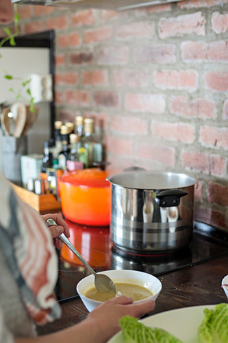 Woman stirring bowl of soup next to hob