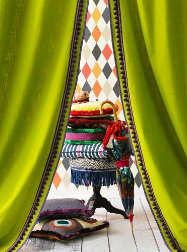 Blick durch grüne Vorhänge auf buntes Deko-Arrangement
