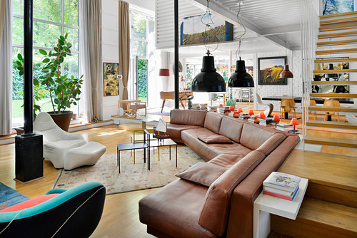 Brown leather corner sofa and designer armchairs in open-plan interior