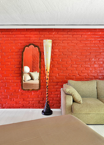 Designer standard lamp and sofa next to mirror on red-painted brick wall