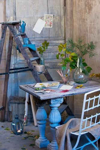 Autumnal arrangement on desk in front of stepladder used as shelves